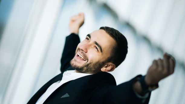 Happy Businessman executive raising fists in excitement in office
