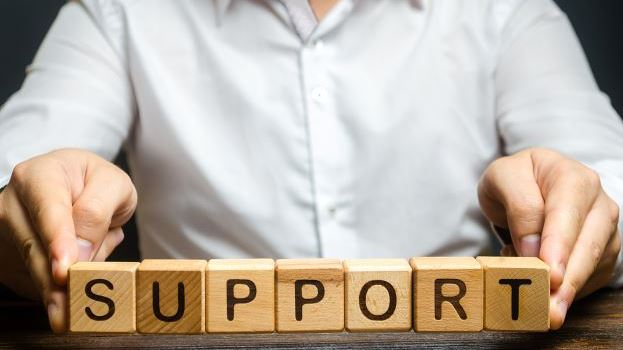 Man holding wooden blocks saying support
