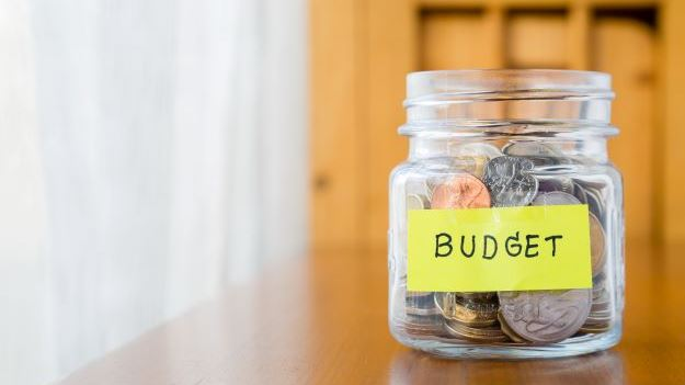 Coins in a jar with a post it note saying budget