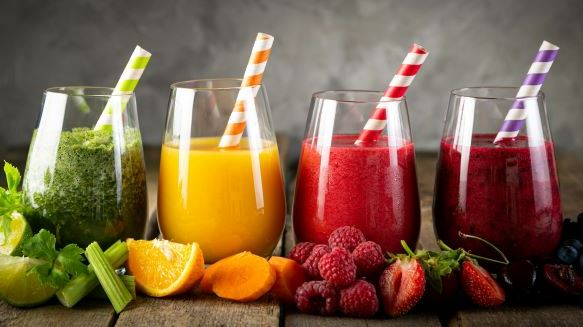 Four different smoothies with the fruit scattered in front of the glasses