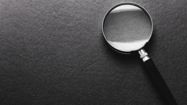 Magnifying glass lying on a black desk